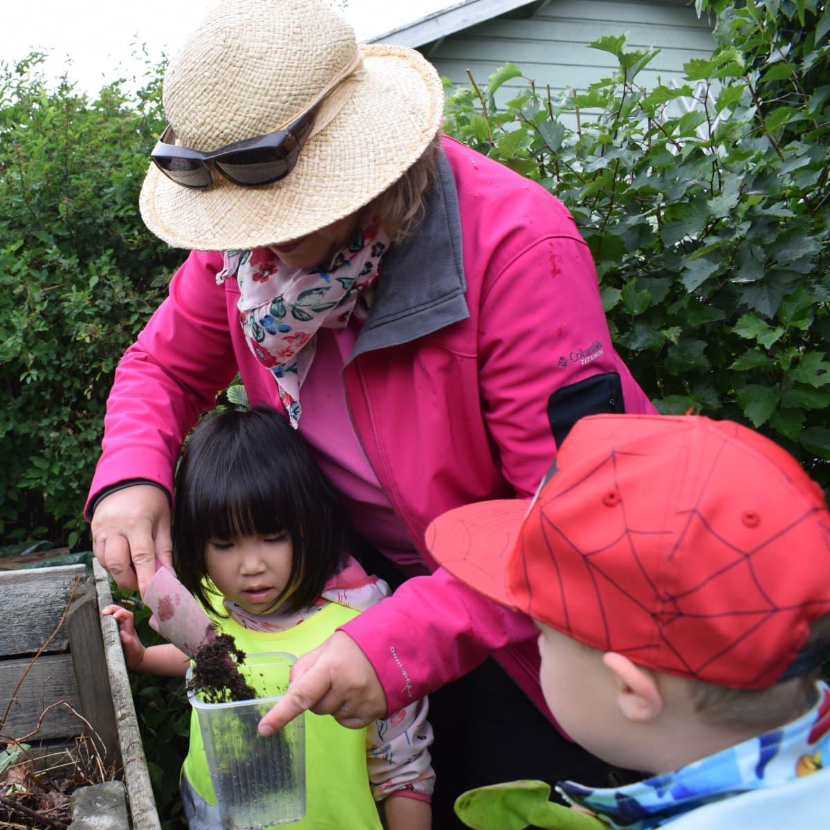 Opettaja ja kaksi lasta tonkii kompostia.