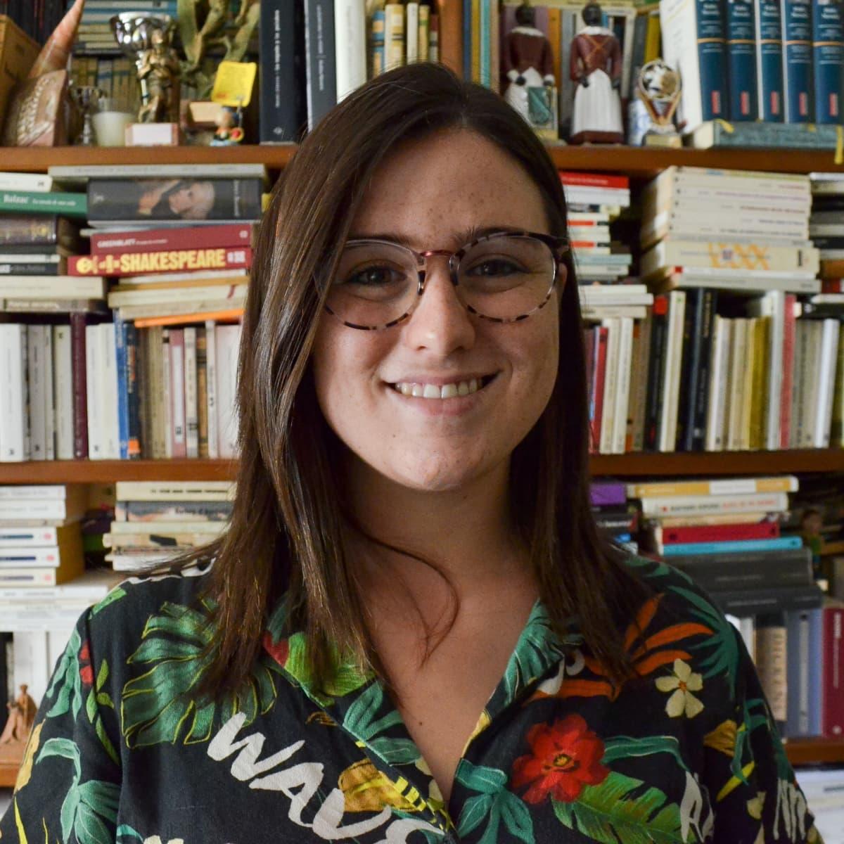 Espanjalainen Lucia Sanz Astier tulee Suomeen kesällä varhaiskasvatuksen opettajaksi. Kuvassa hän hymyilee kirjahyllyn edessä.