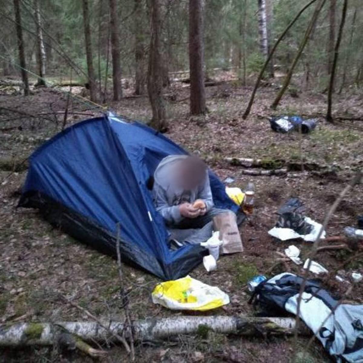 Kuvassa on teltta metsässä. Puoliksi teltasta ulkona istuu mies. Rinkka ja muita tavaroita on levitelty teltan ympärille. Miehen kasvot on sumennettu anonymiteetin varmistamiseksi.