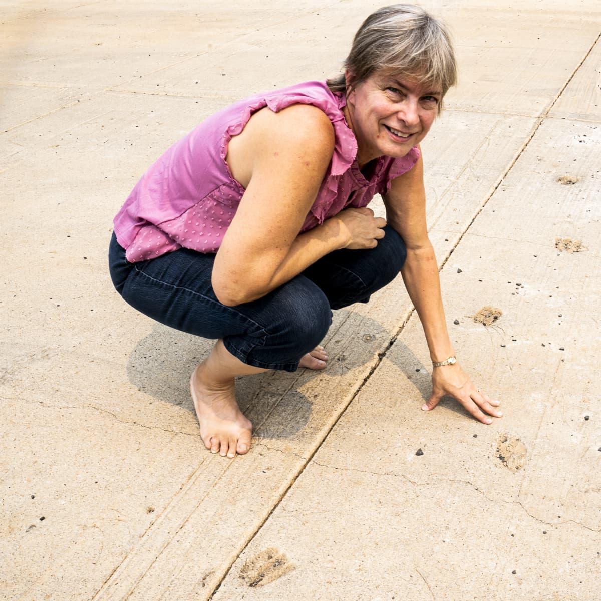Nainen koskettelee betonilaattaa.