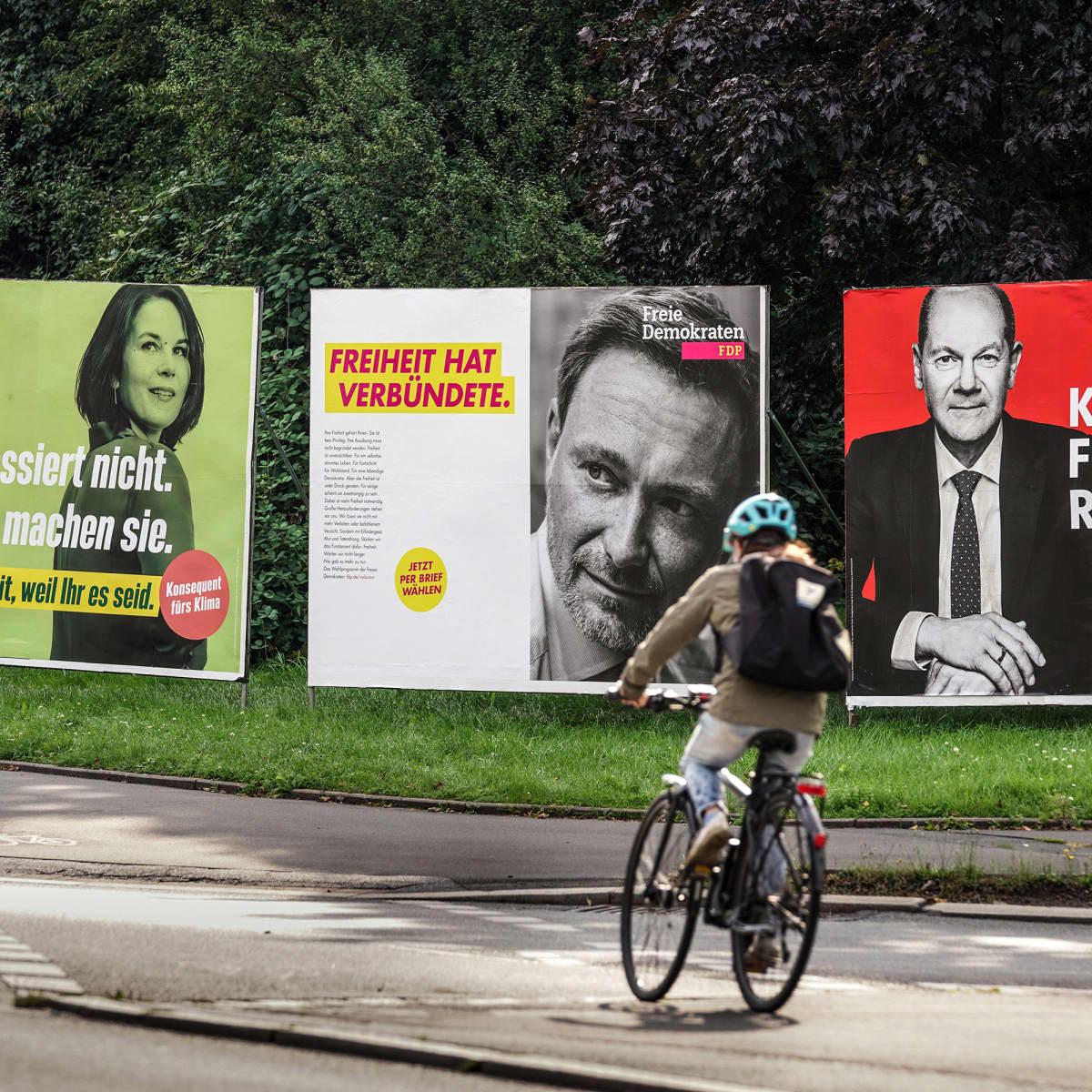 Polkupyöräilijä polkee vaalijulisteiden ohtise.