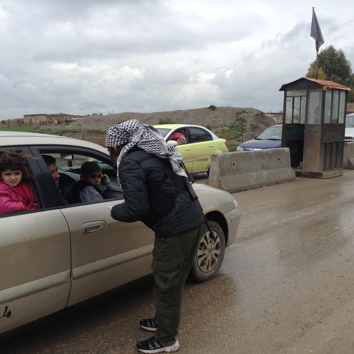 Derikin ulkpuolella turvallisuusjoukkoihion kuuluva nainen tarkistaa ajoneuvoja.