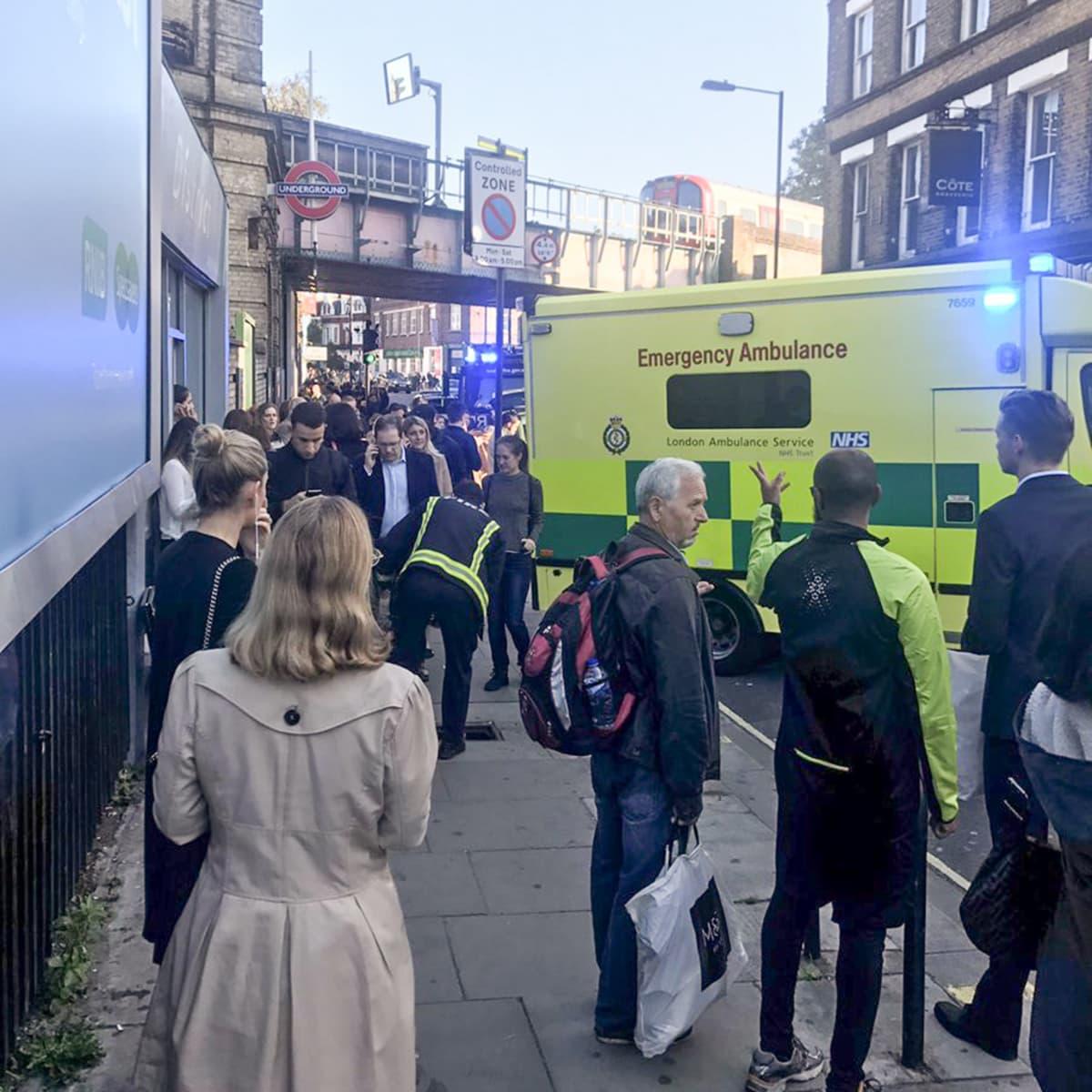 ihmisiä ja ambulanssi kadulla
