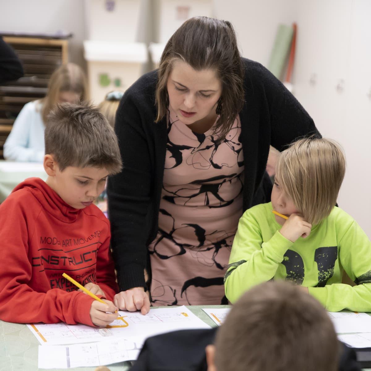 Opettaja neuvoo oppilaita tunnilla.