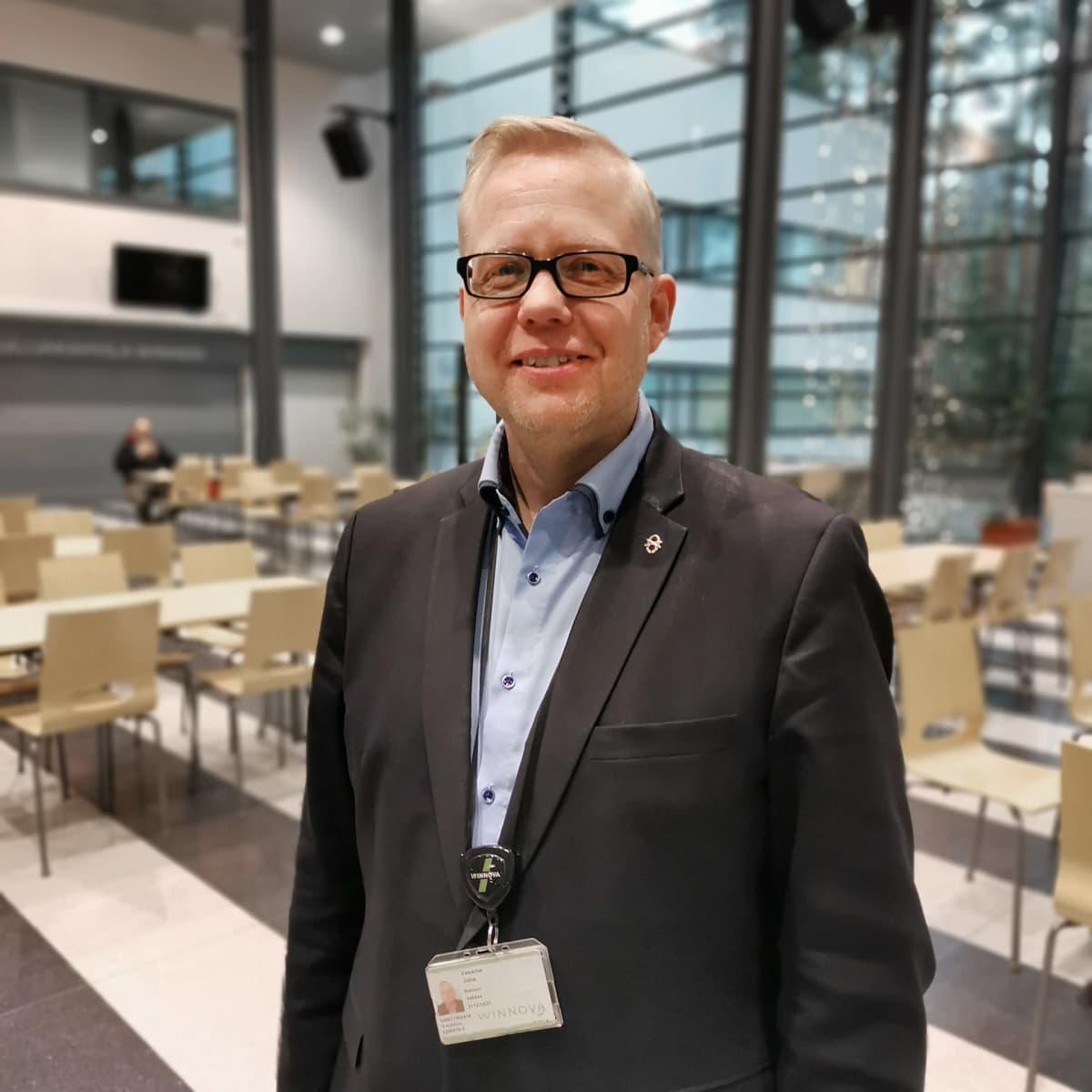 Juha Vasama seisoo koulun ruokalassa