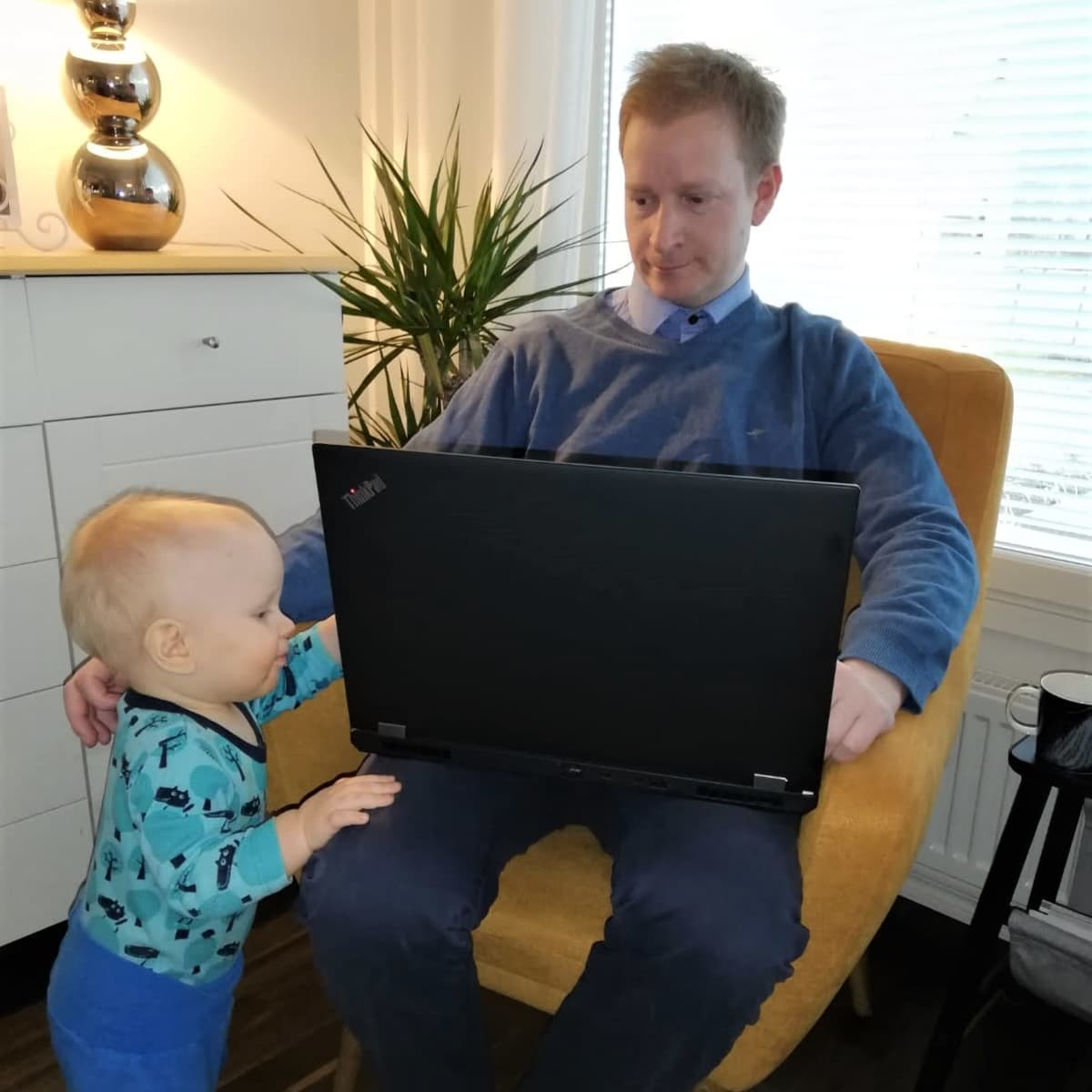Olli Lehtonen istuu nojatuolissa läppäri sylissä ja Filip-vauva pyrkii syliin.