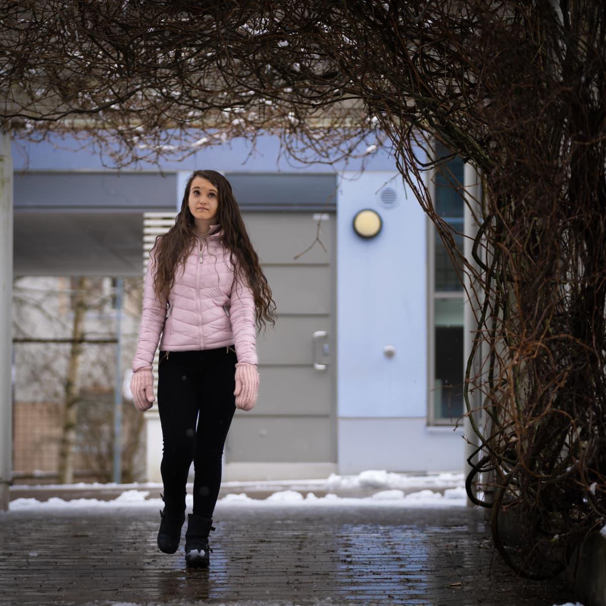 Opiskelija Janika Angelsola kävelee kerrostalon pihalla.
