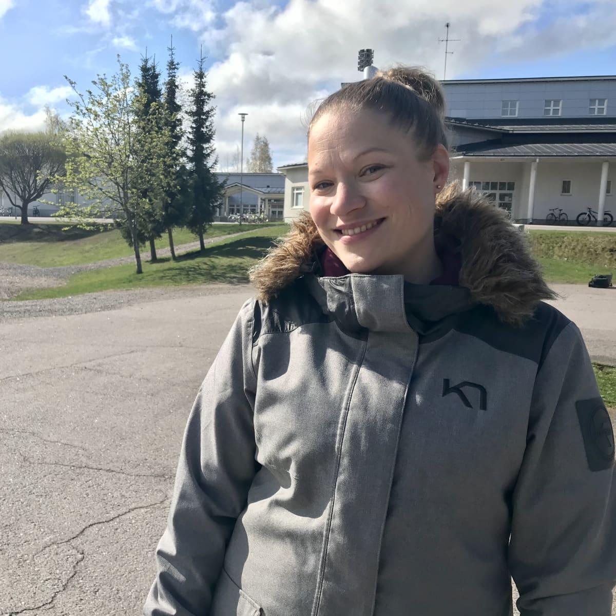 Anna-Kaisa Auvinen seisomassa koulun pihalla.