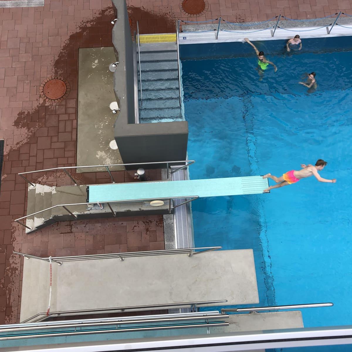 Poika hyppää ponnahduslaudalta uima-altaaseen.