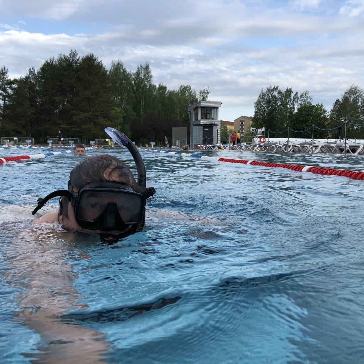 Mies snorklaa uima-altaassa.