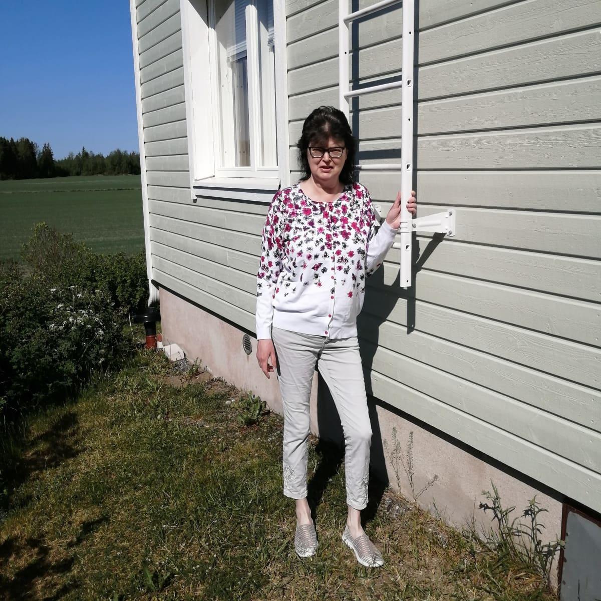 Marjo Torkkeli talonsa edessä.