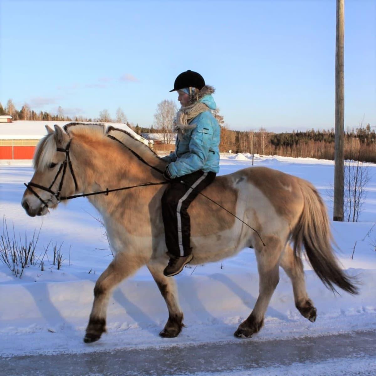 Nainen ratsaa jäisellä tiellä ilman satulaa.
