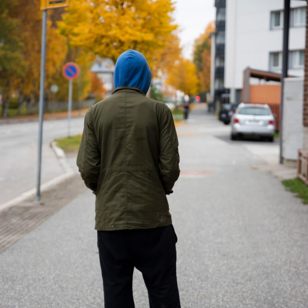 Huppupäinen mies kävelee kadulla.