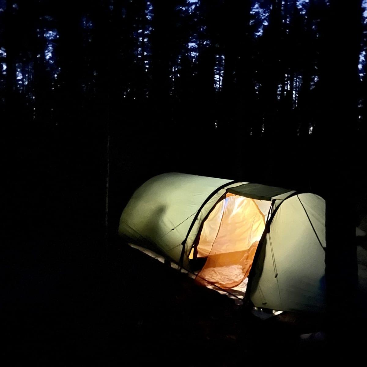 Valaistu teltta loistaa pimeässä metsässä. Teltan sisällä näkyy ihmisen varjo.