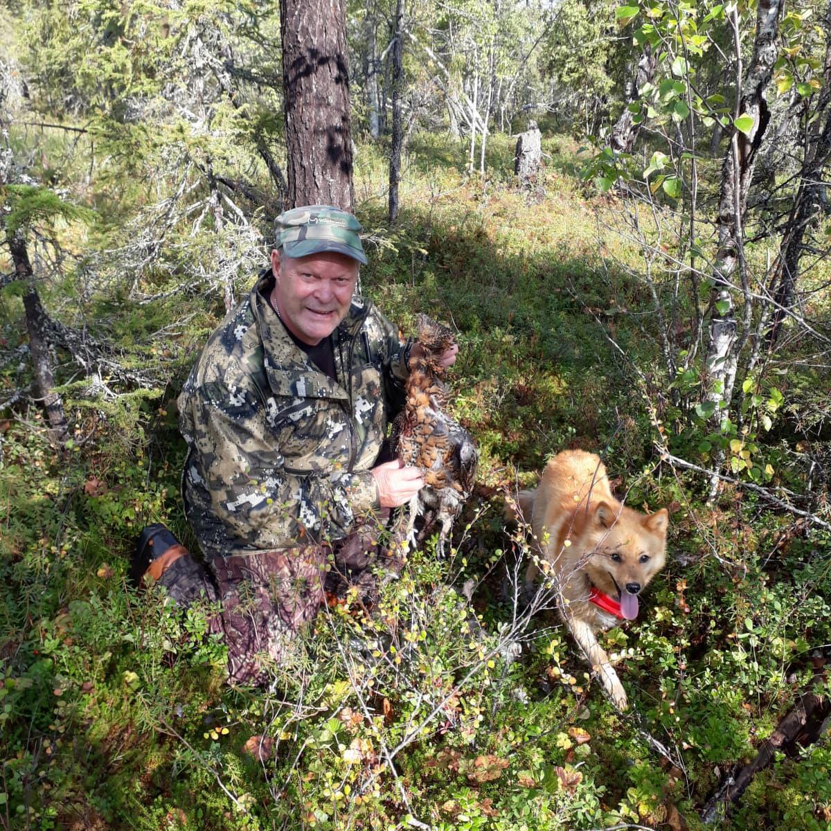 Maastopukuinen Raimo Johansson pitelee ampumaansa koppeloa, vieressä suomenpystykorva.