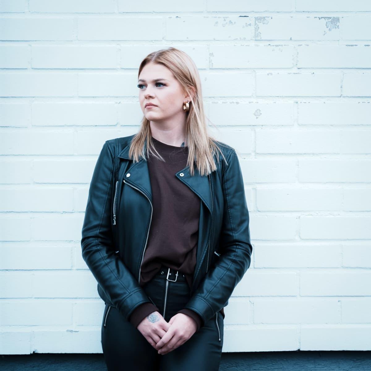Emma Syrjälä nojaa betoniseinää vasten.