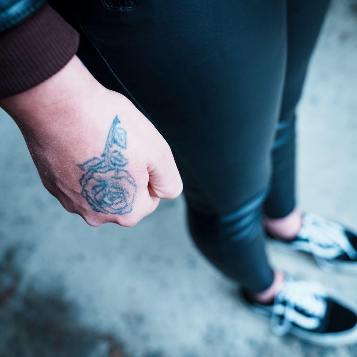 Käsi, jossa on ruusutatuointi on nyrkissä