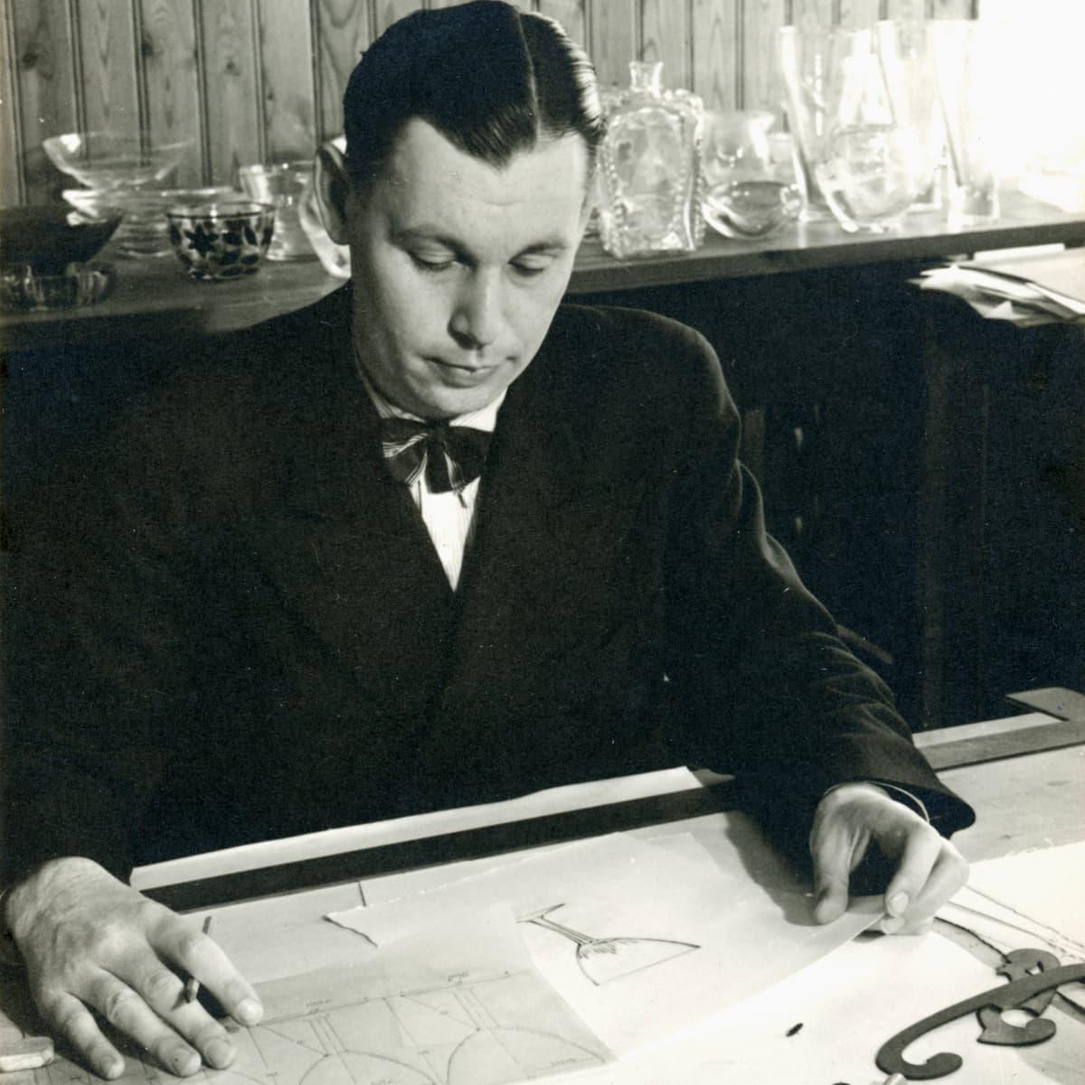 Rusettikaulainen mies istuu työpöydän ääressä piirustuksia edessään