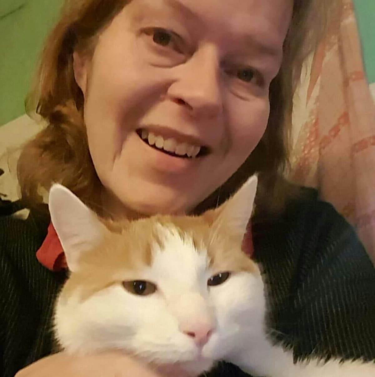 Tiina Autonen poseeraa perheen kissan kanssa.