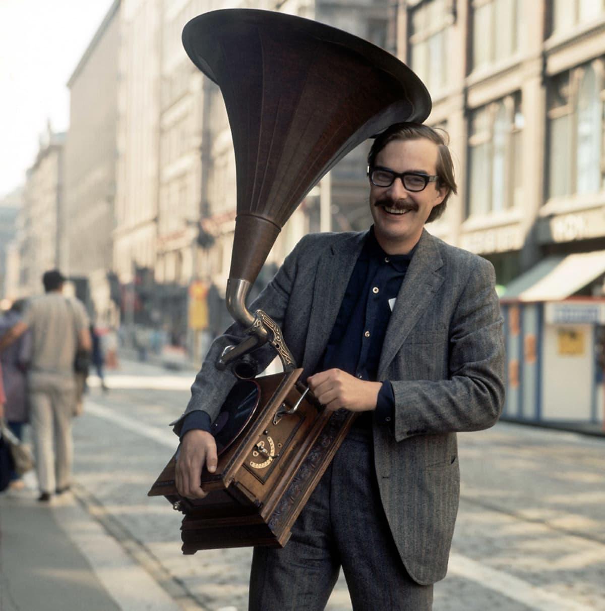 Säveltäjä Henrik Otto Donner kesällä 1970. Hänellä on kädessään käsin veivattava gramofoni, jossa on suuri tummanruskea torvi.