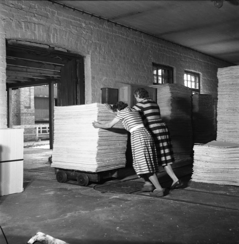 Naiset työntävät pahviarkkipinoja kiskoja pitkin vuonna 1964