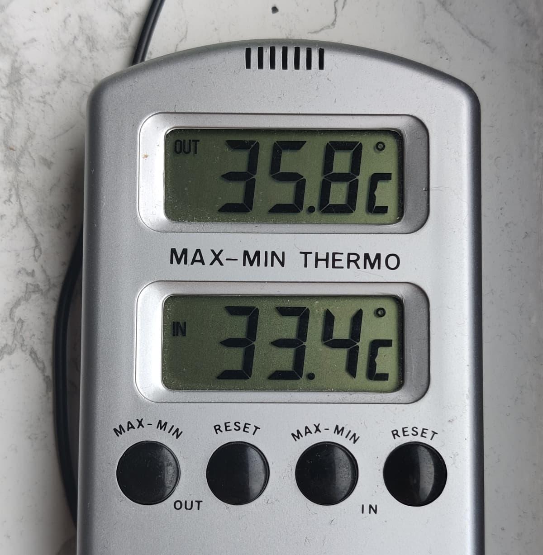 Lämpömittarin lukema näyttää ulkona 35,8 astetta ja sisällä 33,4 astetta.