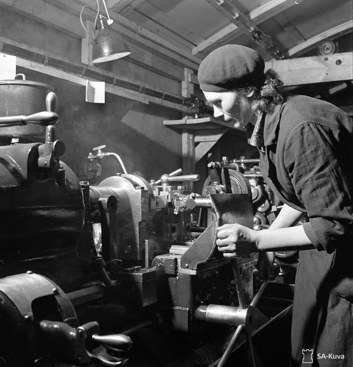 sotatarviketeollisuus, nainen metallisorvin ääressä.