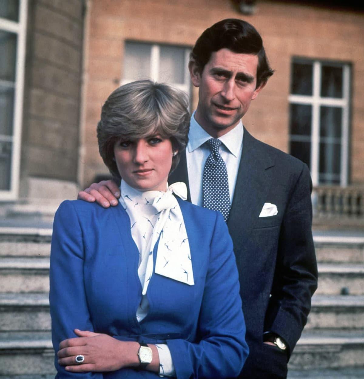 Diana ja Charles seisovat rinnakkain. Charlesin käsi on Dianan hartialla.