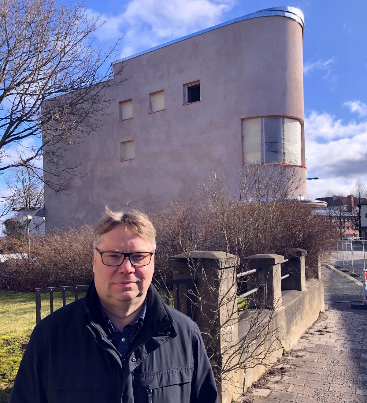 Mies seisoo kuvan etualalla. Takana vanha funkkistyylinen, pyöreäkulmainen rakennus.