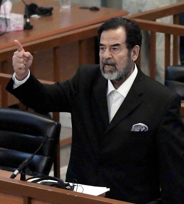 Saddam Hussein oikeudessa sormi pystyssä.