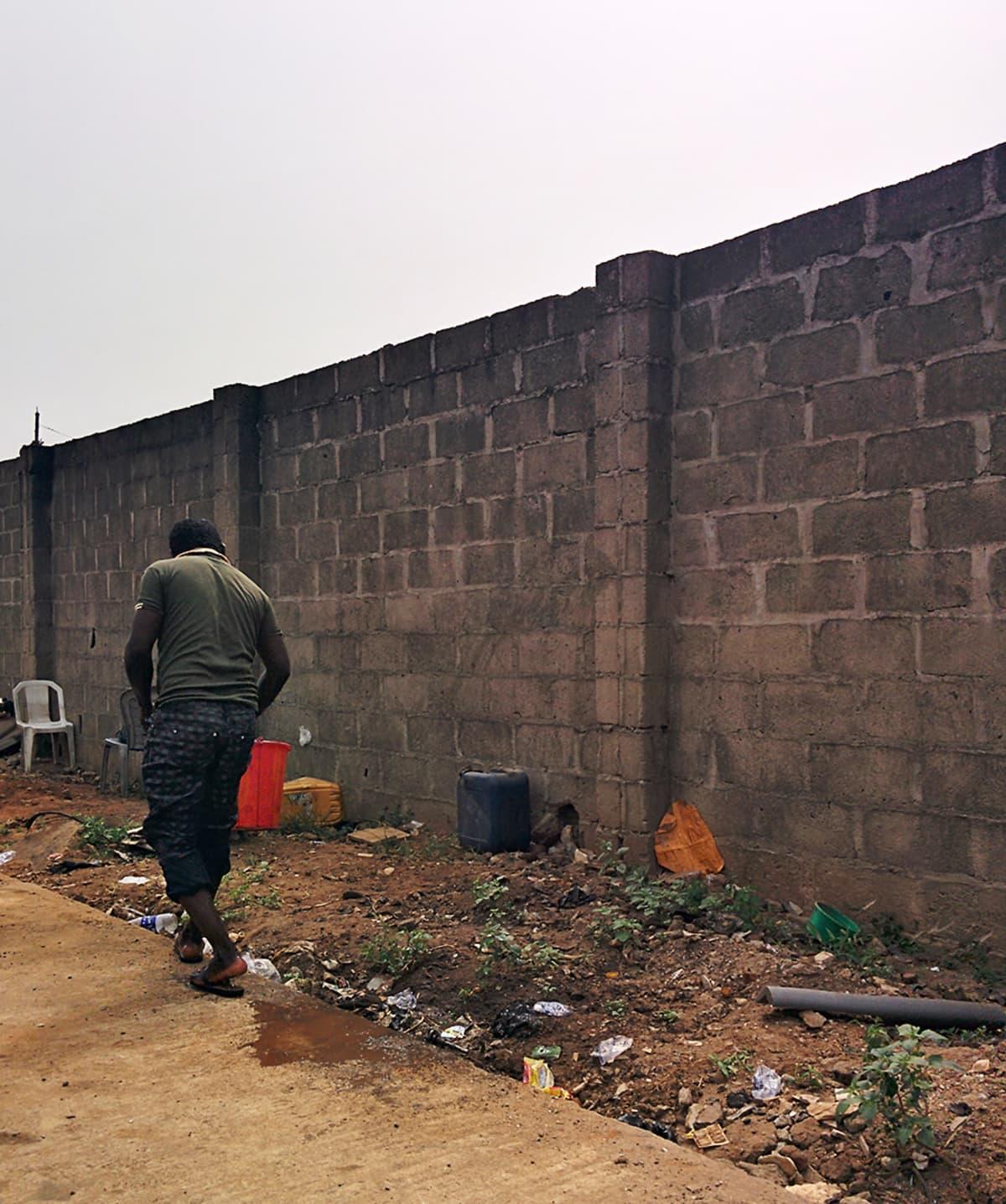 Mies kävelee lähellä muuria, jonka viereen on kasattu epämääräisiä roskia.
