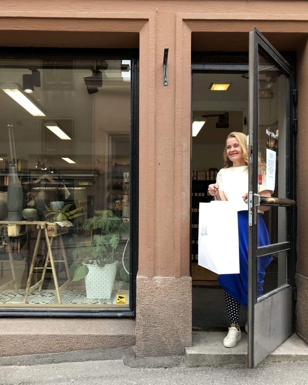 yrittäjä Mari Nieminen ojentaa paperipussin oven suusta