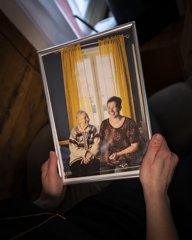 Kädet pitelevät kuvaa, jossa Vuokko Lahti ja hänen isoäitinsä hymyilevät iloisesti.