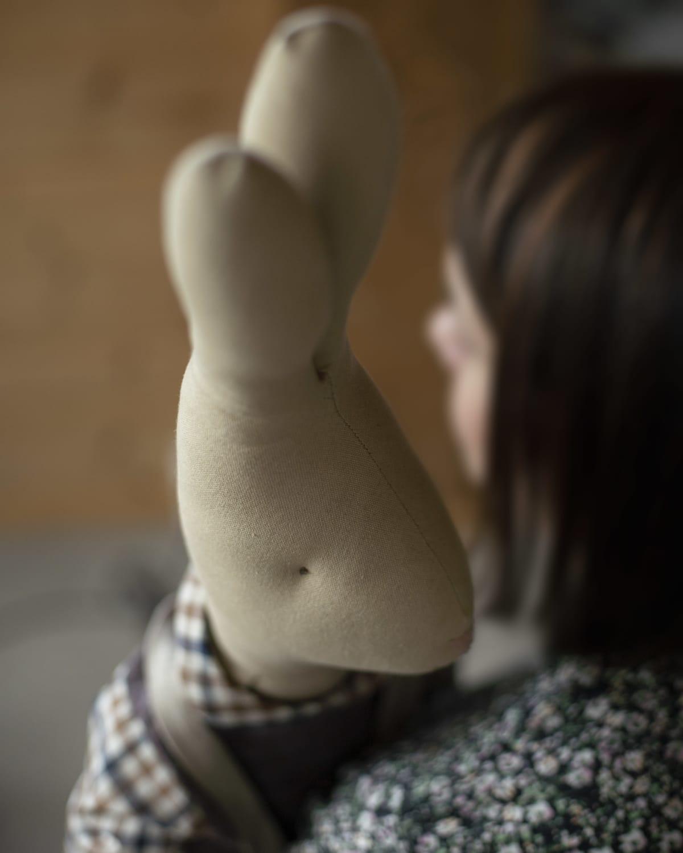 Nainen pitelee pupu pehmolelua sylissään.