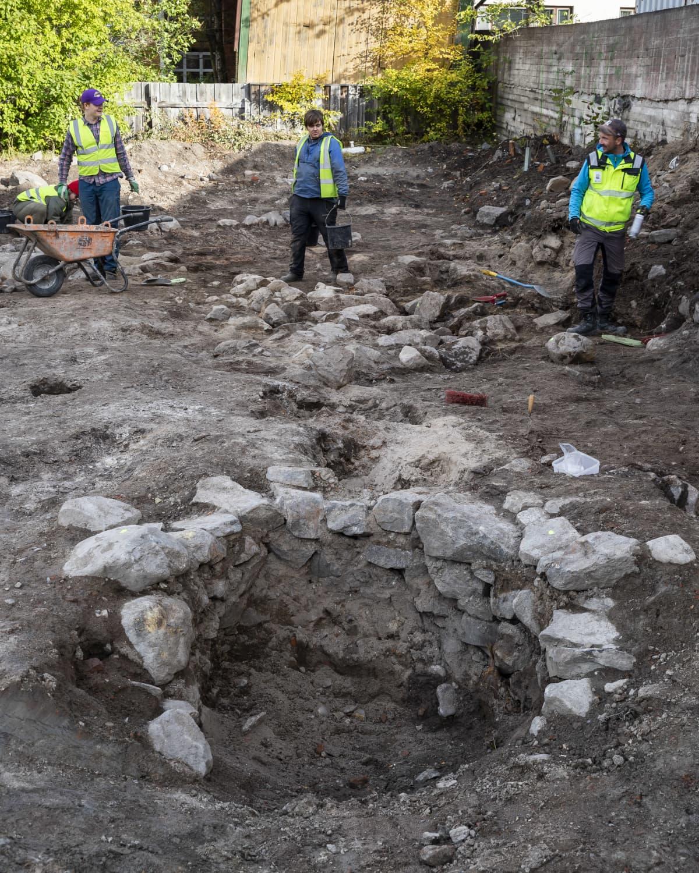 Etualalla kuvassa on kaivo. Taaempana kolme arkeologia suorittamassa kaivauksia.