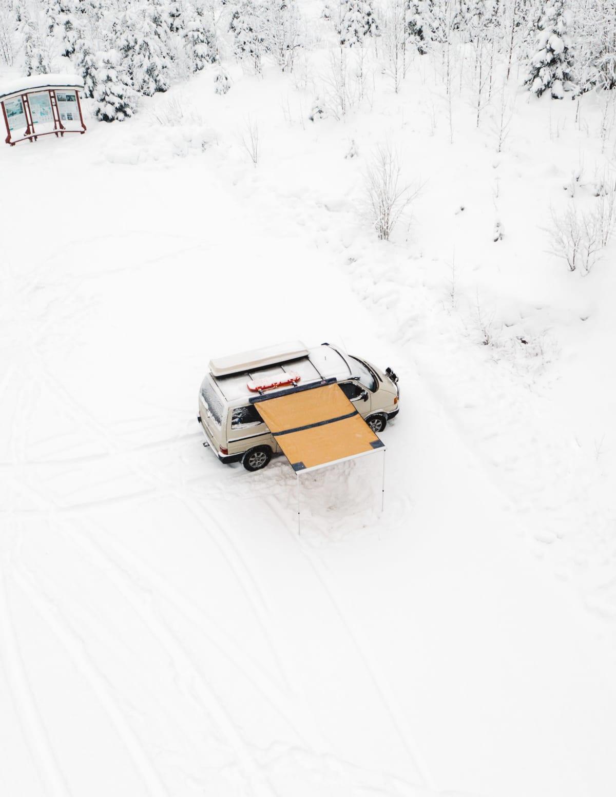 Reissupaku lumisella parkkipaikalla ylhäältäpäin kuvattuna.