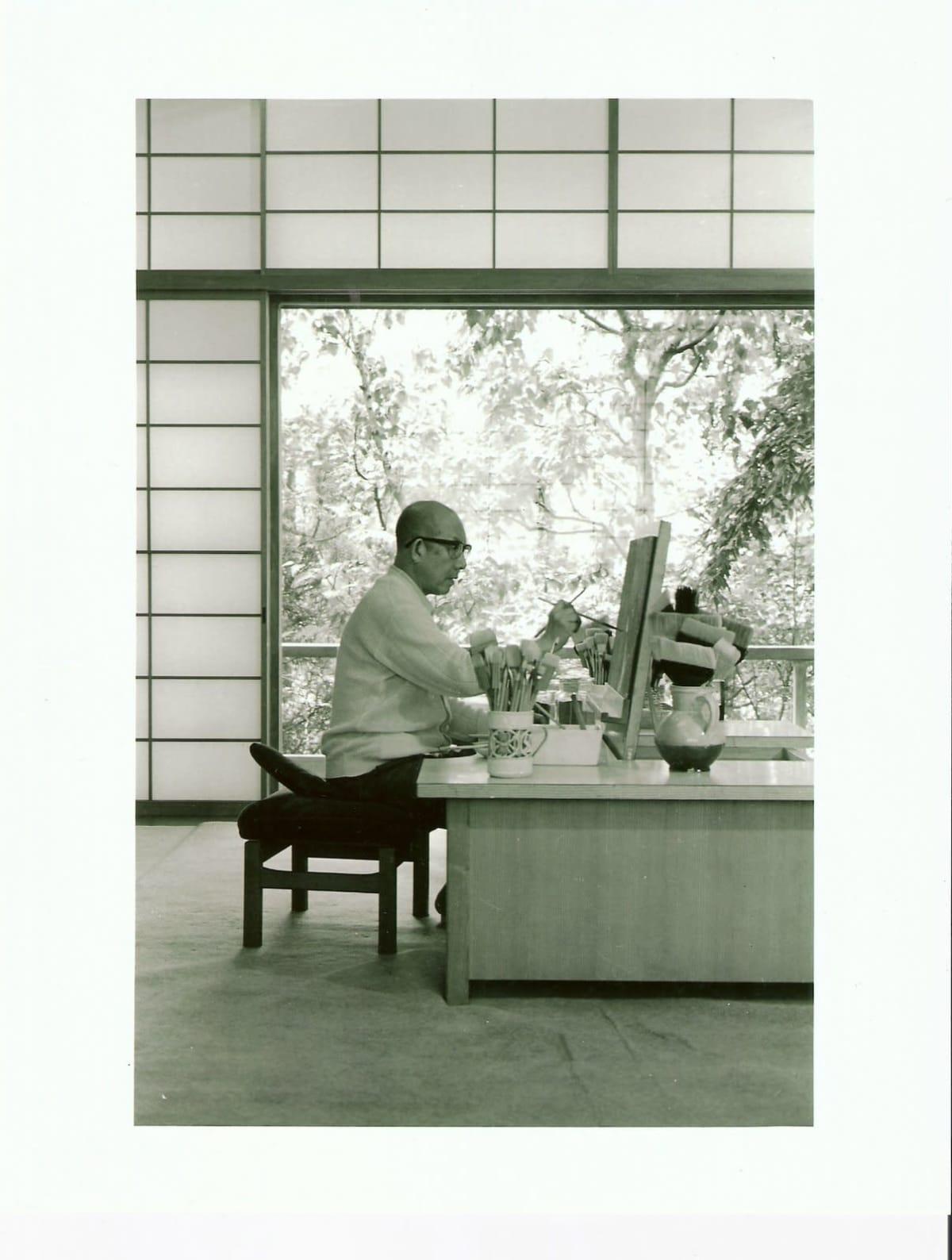 Kaii Higashiyama istuu työpöydän äärellä kotiateljeessaan Ichikawassa vuonna1988.