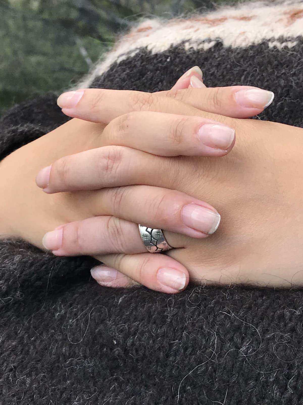 Naisen kädet ristissä vatsalla ruskean villapaidan päällä