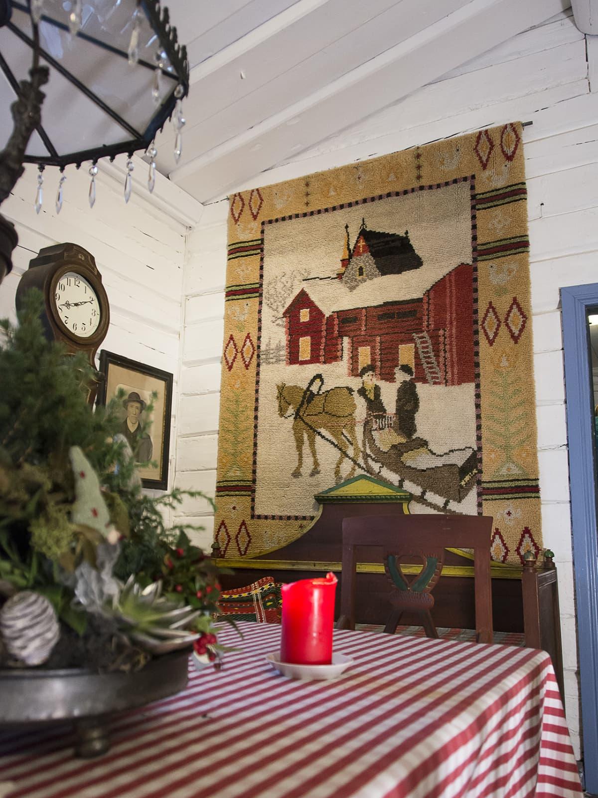 Seinällä olevan ryijy, jossa kuva kahdesta henkilöstä hevosreen kanssa lumisessa maisemassa.
