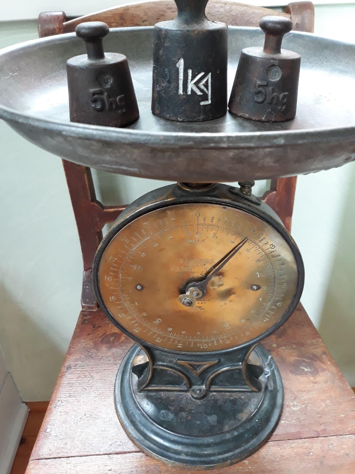 Kuvassa vanha vaaka ja yksi kilon ja kaksi puolen kilon punnusta.