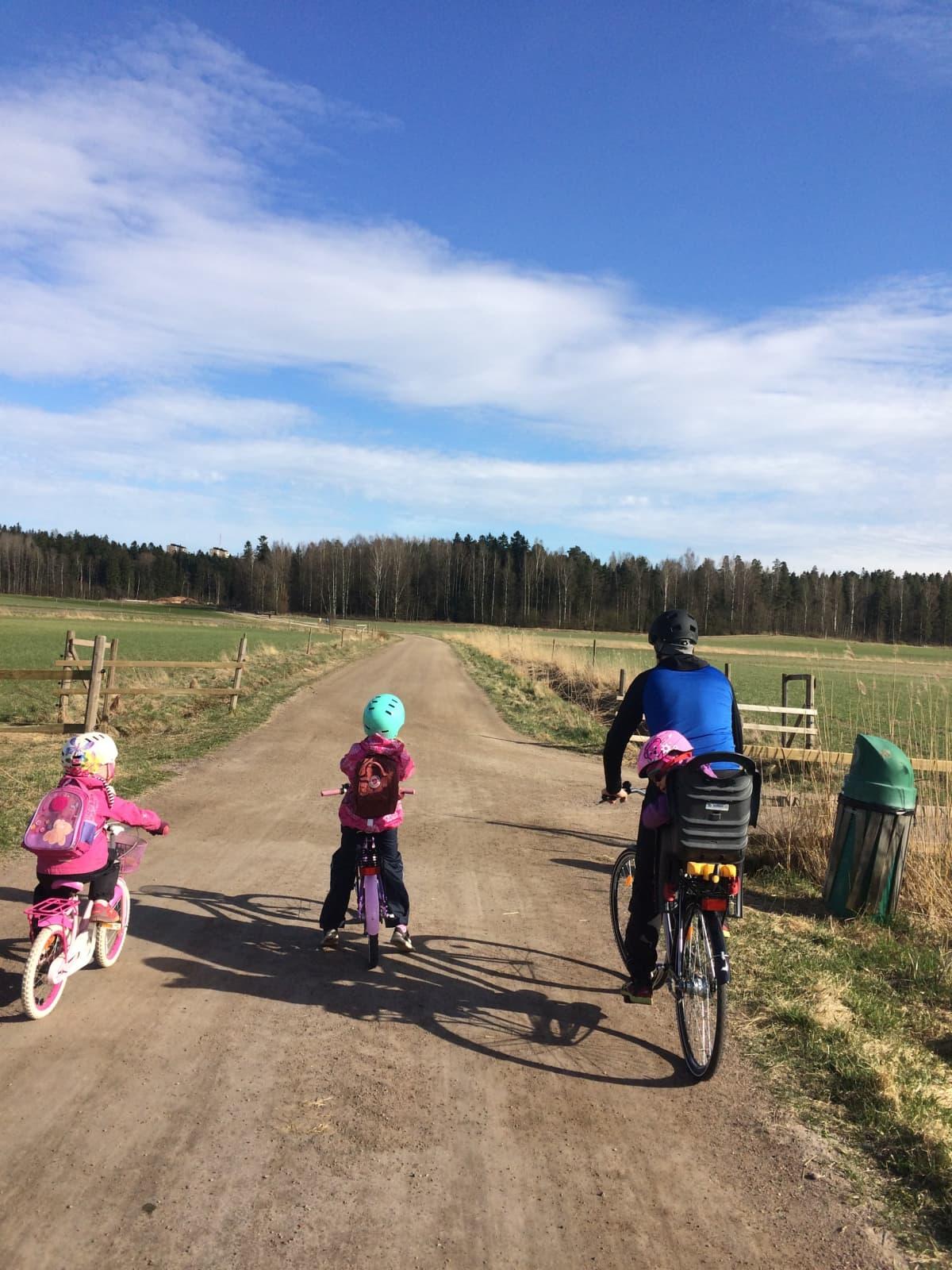 Isä ja kolme lasta pyöräretkellä.