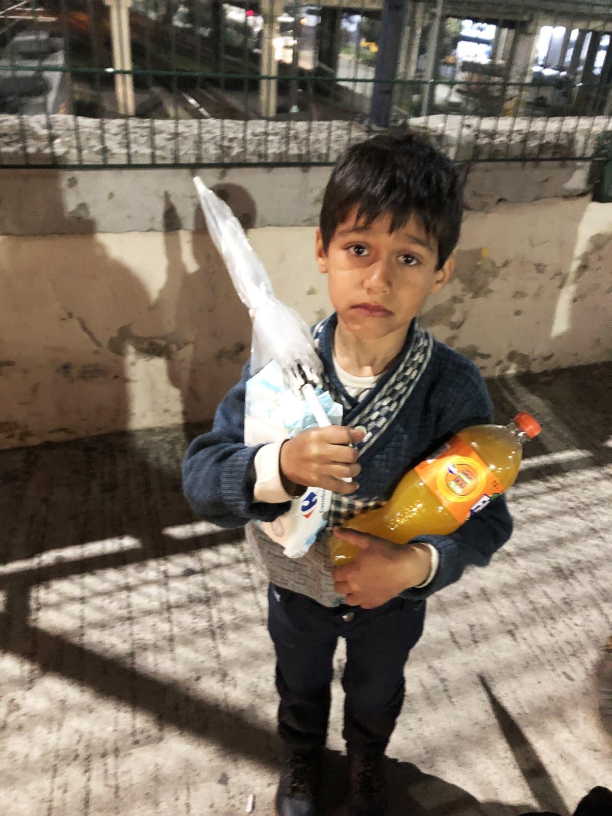 Poika pitelee limsapulloa ja ruokatarvikkeita.