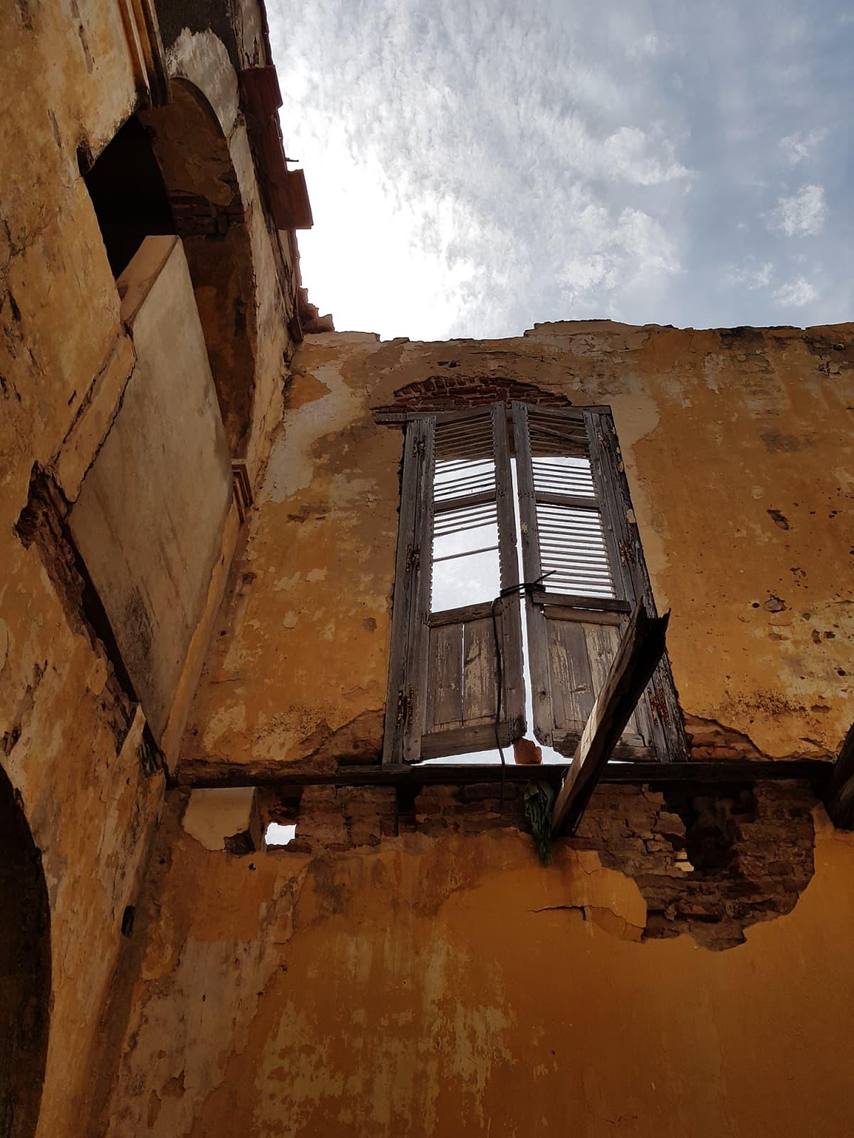 Kuvassa on talon seinä ja toisen kerroksen puinen ovi, jonka takana näkyy taivas.
