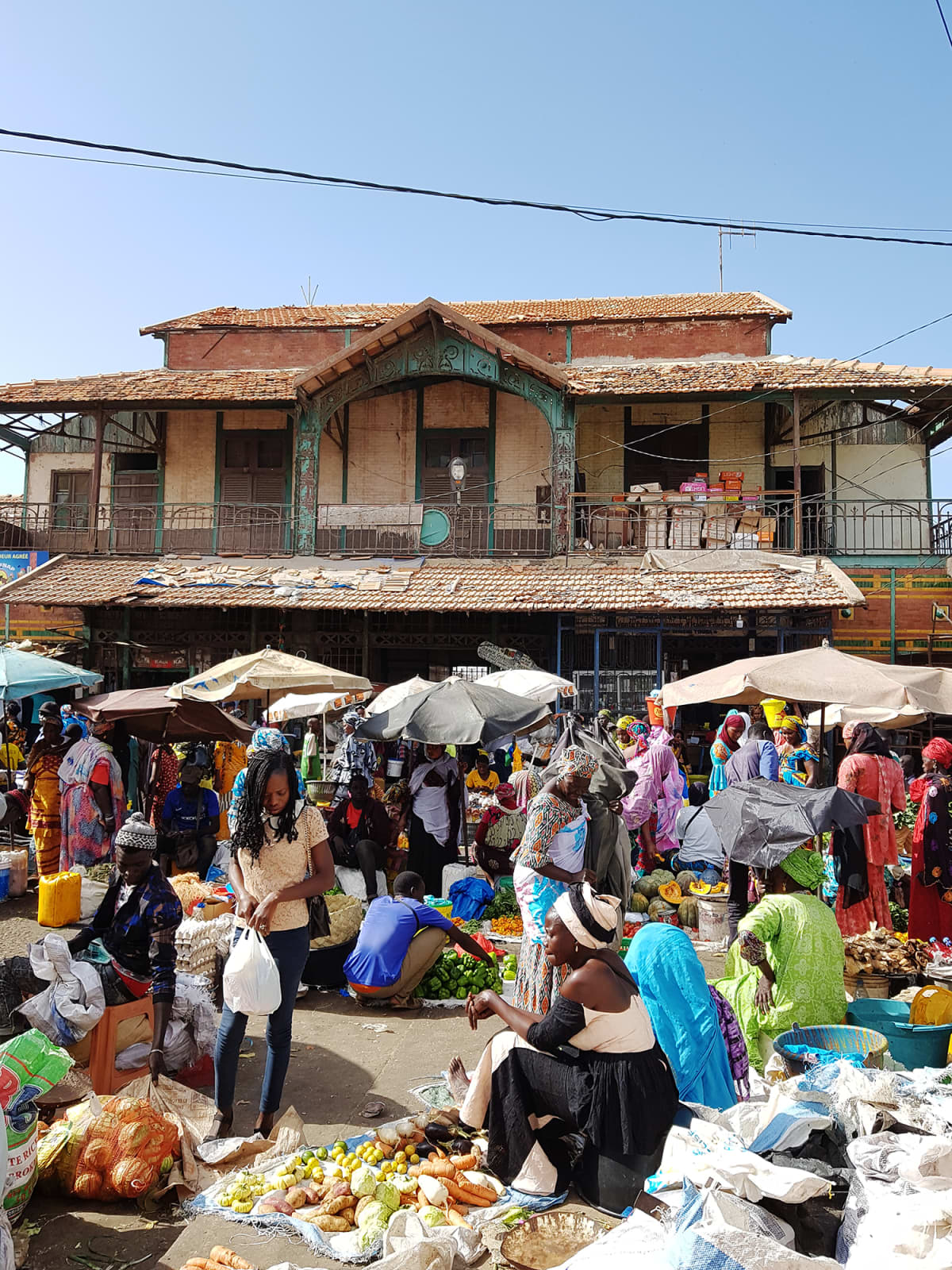 Kuvassa on taustalla siirtomaa-aikainen rakennus ja edessä hedelmä- ja vihannestori, myyjiä ja asiakkaita.