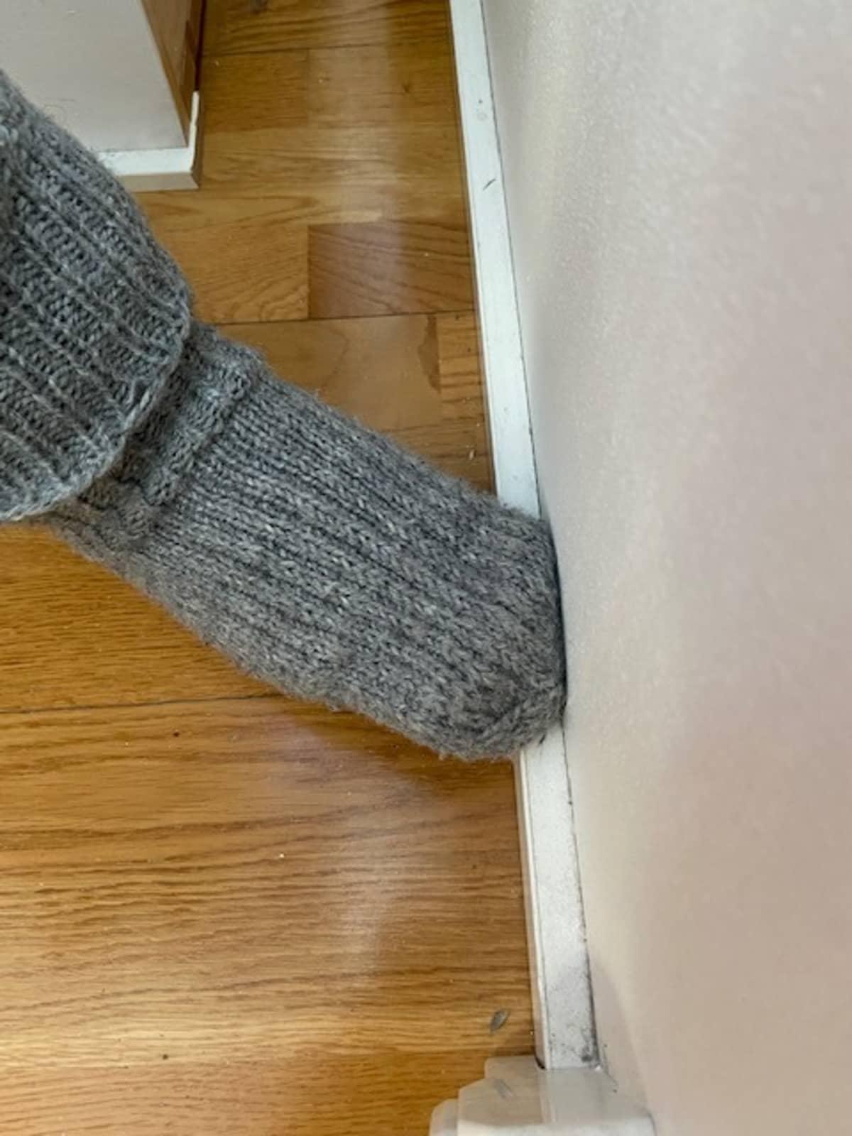 Jalkalistan pölynpyyhintää jalassa olevalla villasukalla.