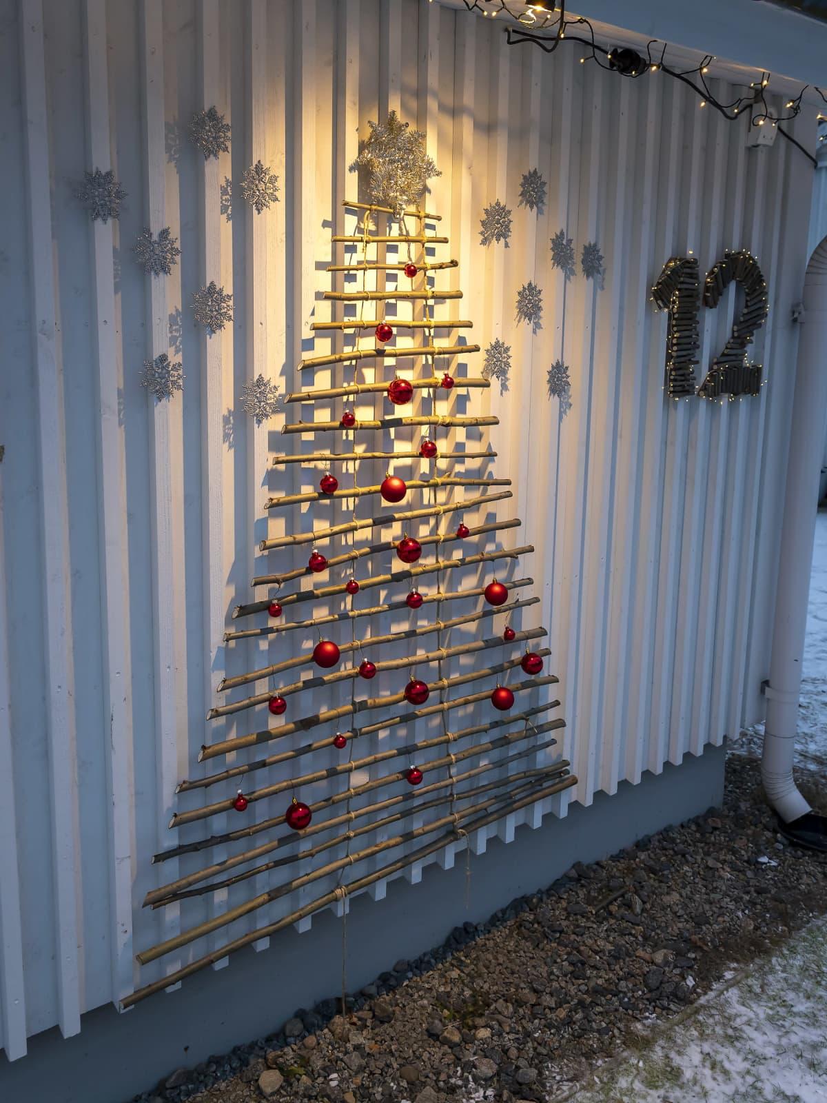 Luukku 12, joka on kepeistä  tehty joulukuusi talon seinällä.