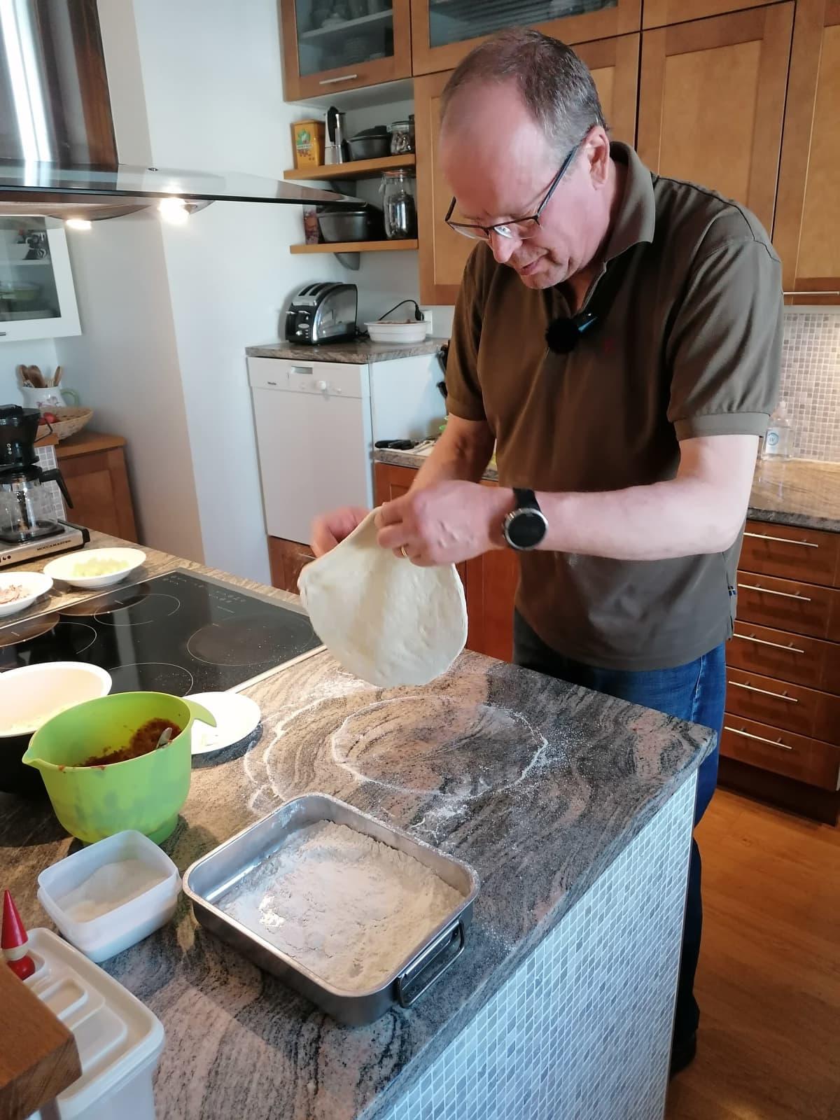 Juha Sivonen tekee pizzapohjaa kotikeittiössään.
