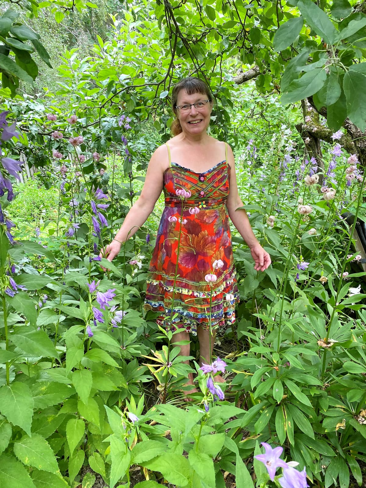 Bilogi Kirsi Kuoppamäki puutarhassa ukonkellojen keskellä.