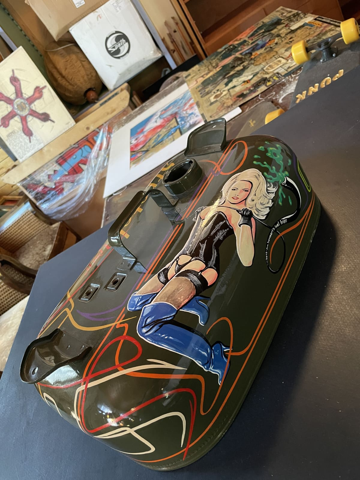 Vanhan bensakanisterin kylkeen on maalattu naisen kuvan.
