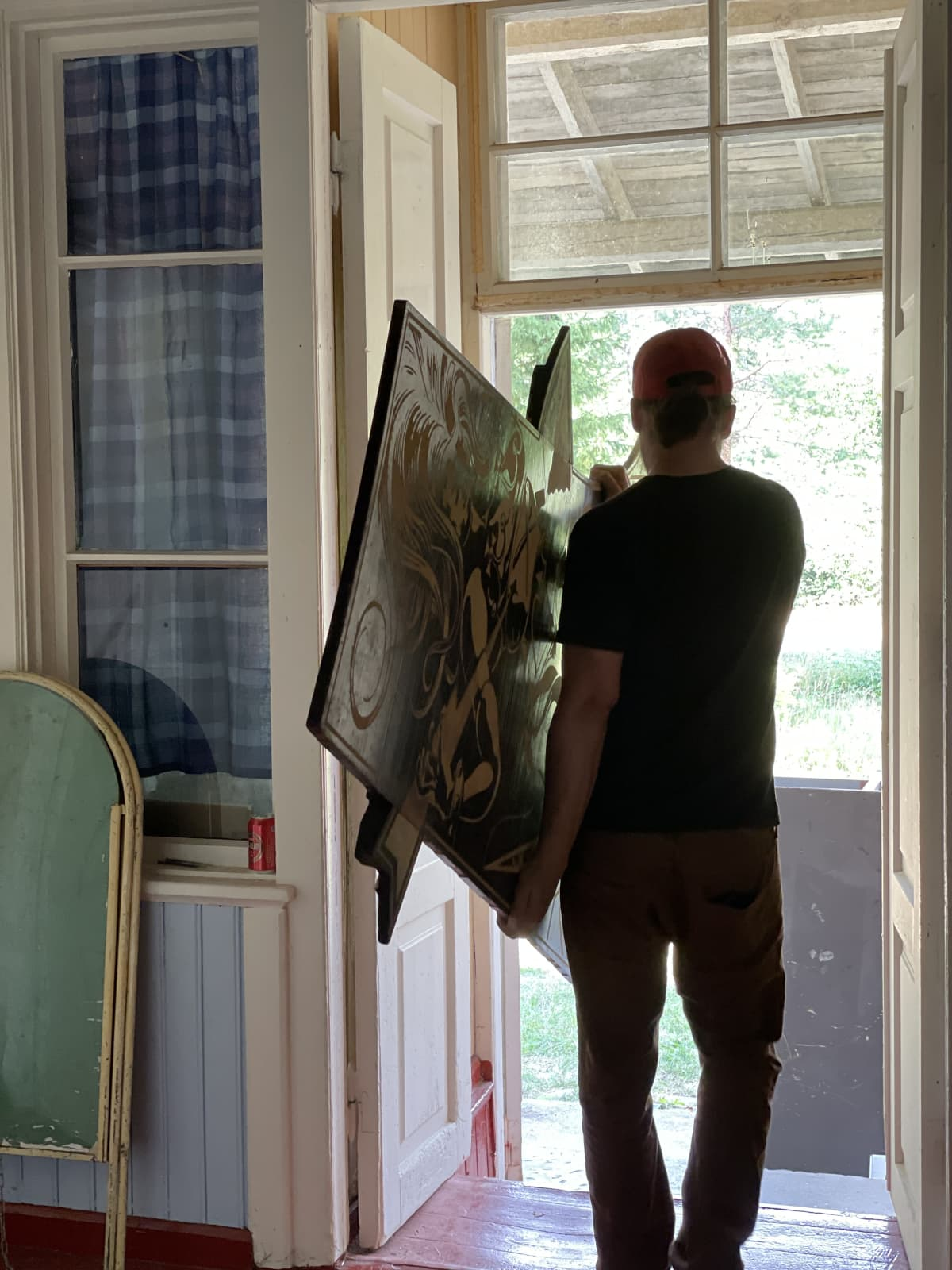 Joona Hamm kantaa isoa teosta ulos ovensuussa.